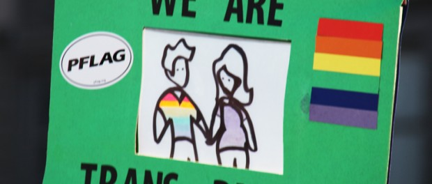 A sign with a drawing of a family, informing the viewer that WE ARE TRANS PARENTS