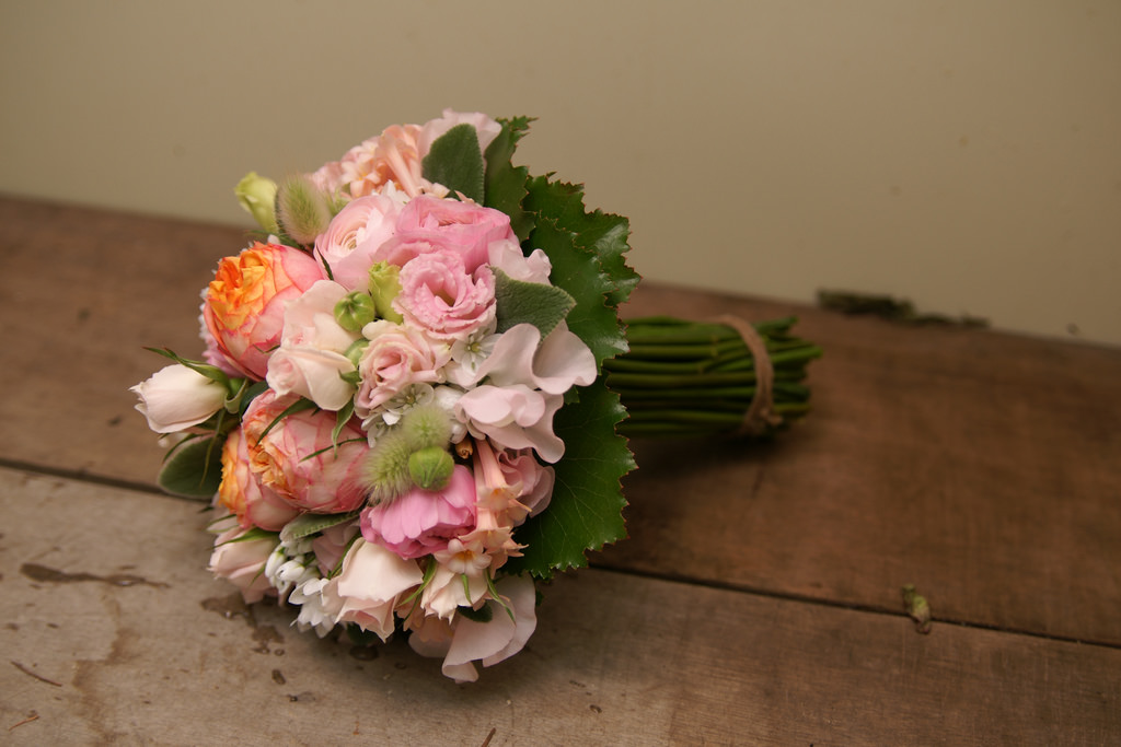 A bouquet lying on a rough wooden table.