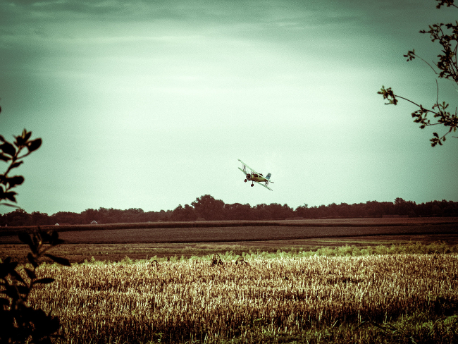 A crop duster sweeping over a field.