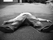 A staged photo of a person lying in the middle of a chalk outline.