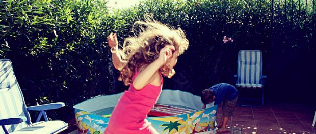 Children playing in a yard on a sunny day.