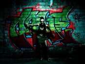 A shadowy figure backlit dramatically against a wall covered in graffiti.