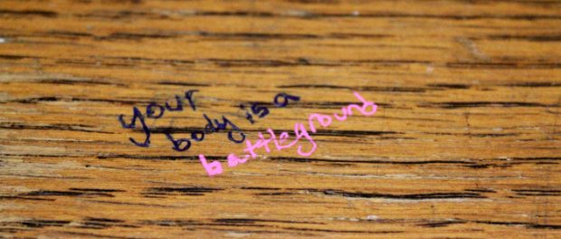 A wooden table, with the words YOUR BODY IS A BATTLEGROUND scrawled across it