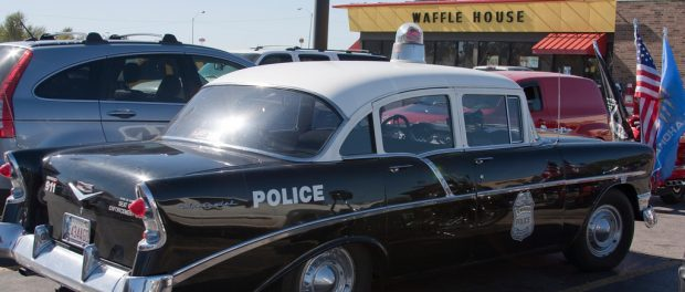 A vintage police car parked outside a Waffle House.