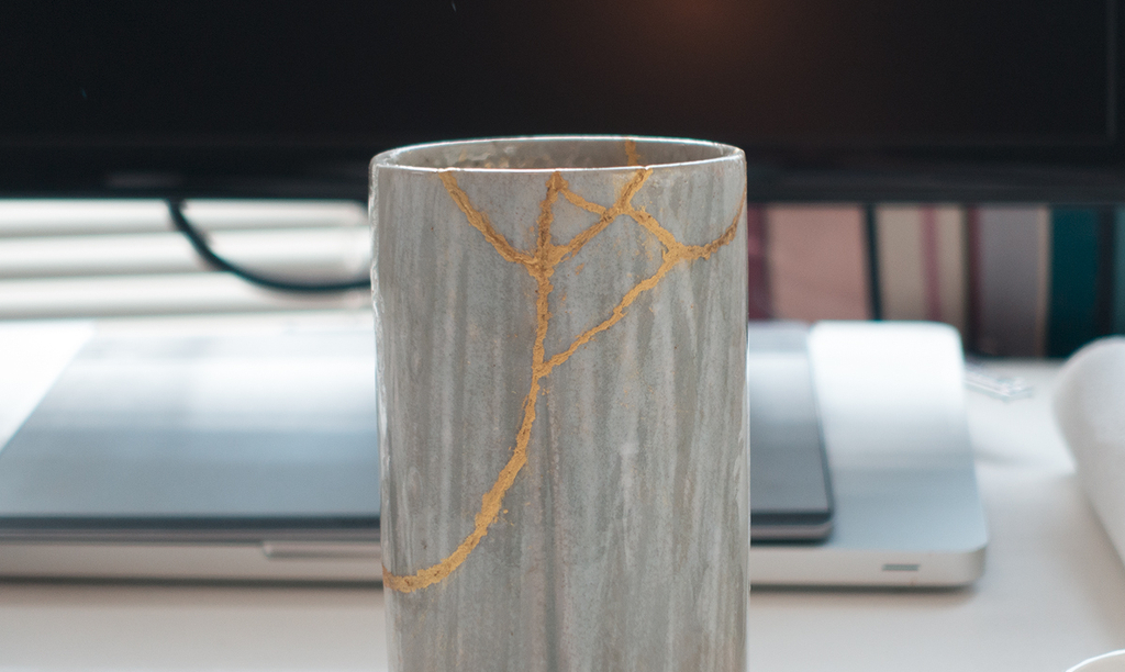 A kintsugi cup that has been broken and glued together with gold seams.