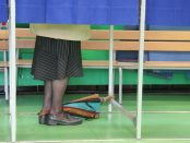 A person in a polling booth. All that's visible is the person's skirt, stockings, and sensible shoes.