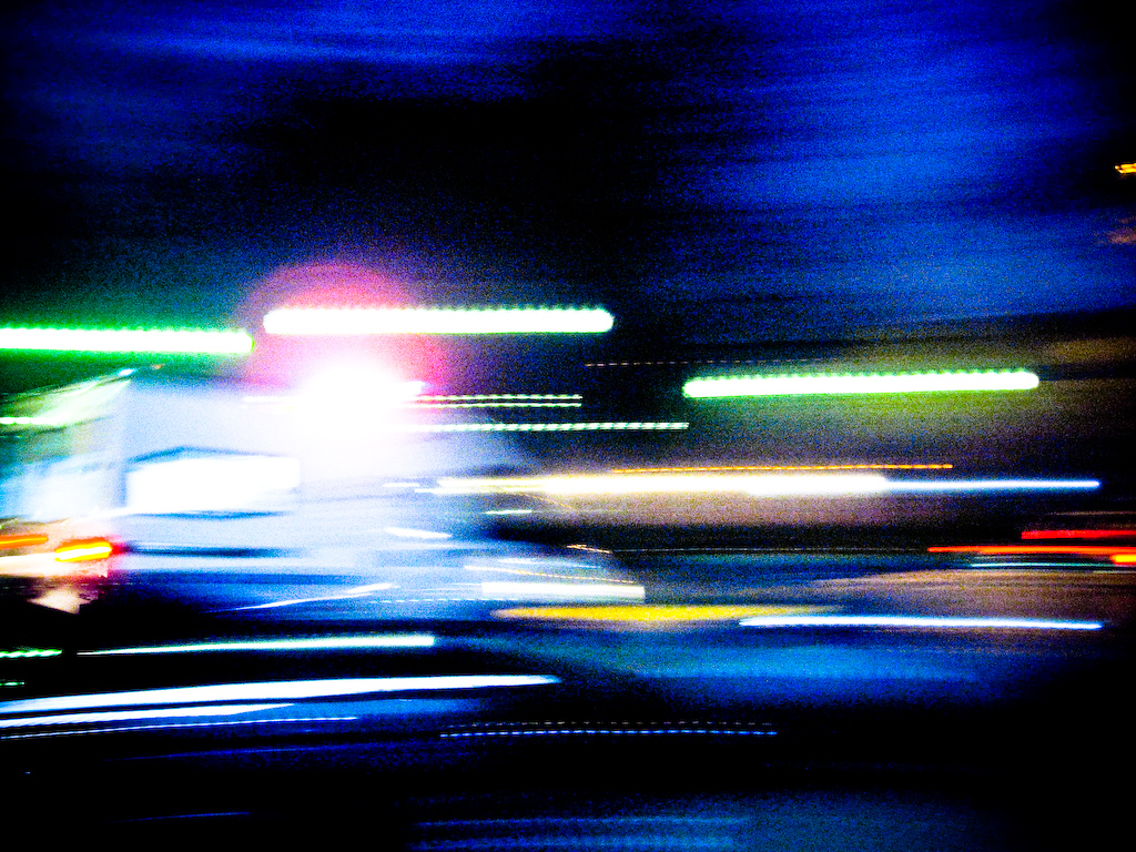 Lights streaking by at high speed as an ambulance moves through traffic.