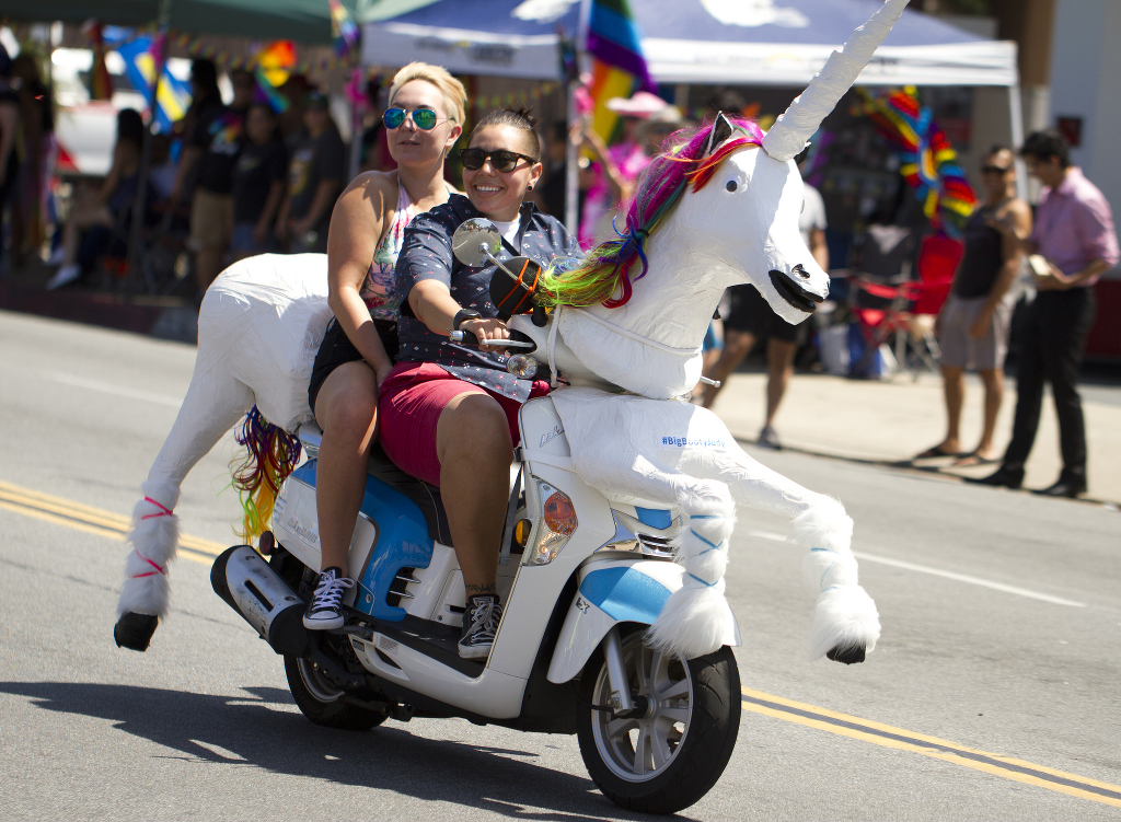 Two people at a Dykes on Bikes march riding a motorcycle outfitted with a unicorn costume.