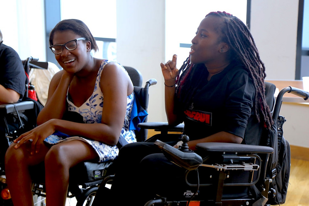 Two dark-skinned wheelchair users in conversation.