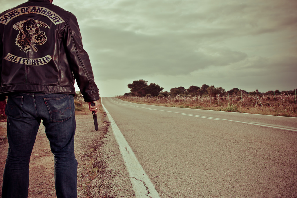 A person in a motorcycle jacket standing by the side of the road.