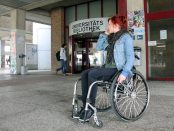 A wheelchair user with bright red hair.