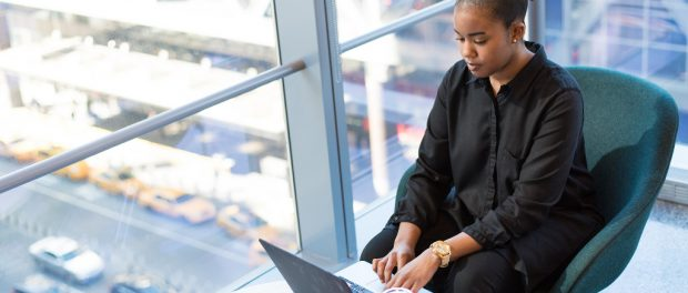 A Black woman with natural hair working on a laptop.