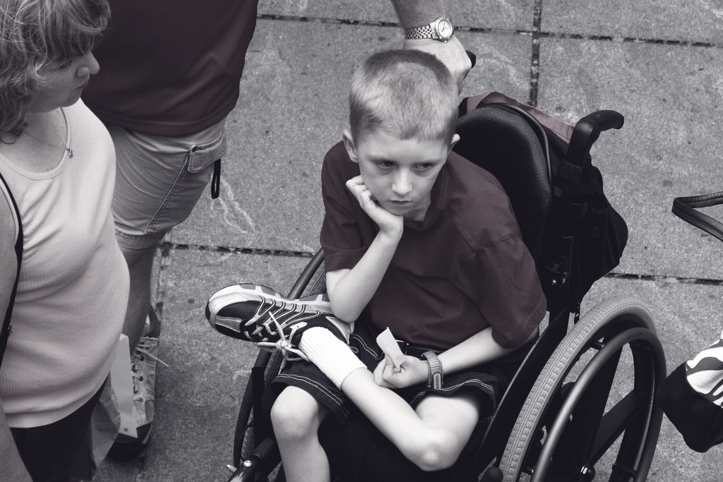 A black and white photo of a kid with a defeated expression sitting in a wheelchair.