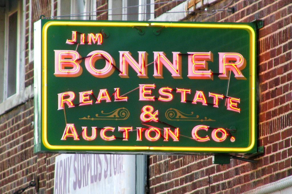 A neon sign outside a real estate office.
