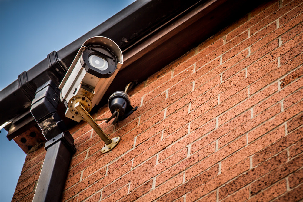A security camera jutting from the facade of a brick building.