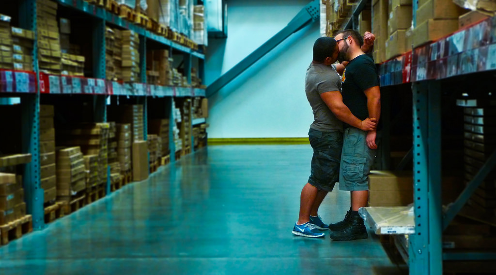 Two men kissing against a row of goods in a warehouse.