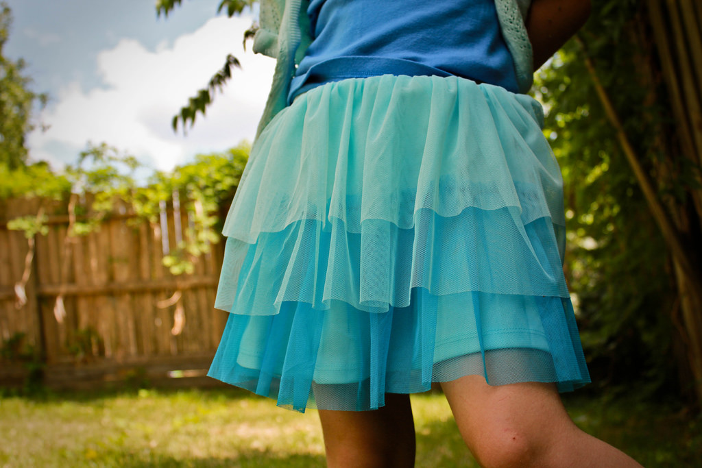 A person wearing a blue layered skirt.