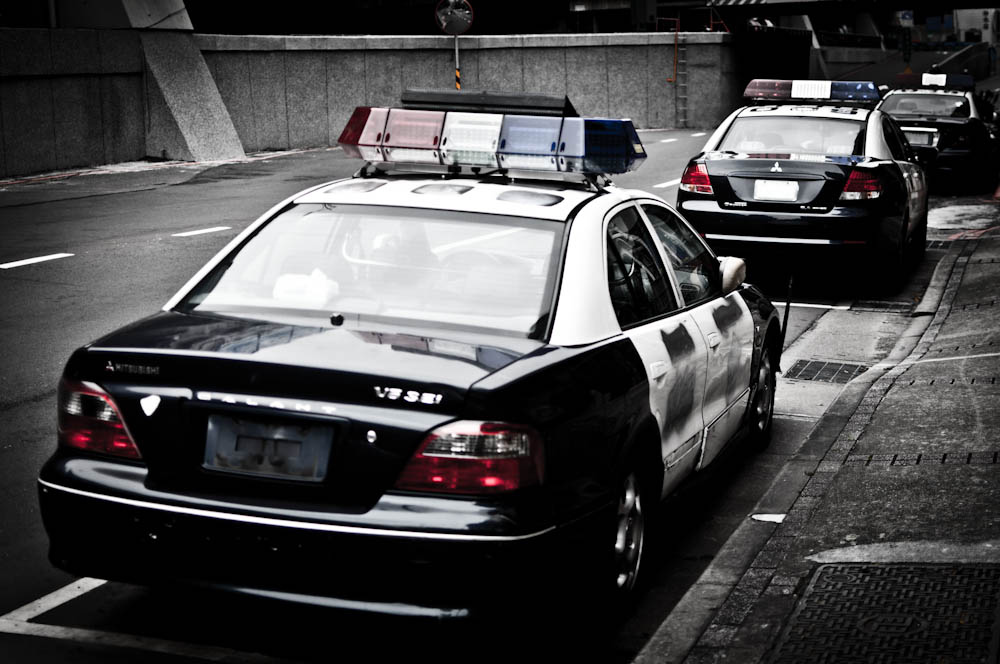 Police cars in a desaturated image.