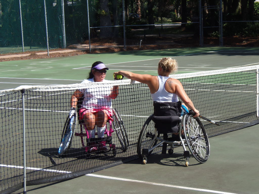 Two wheelchair users playing tennis.