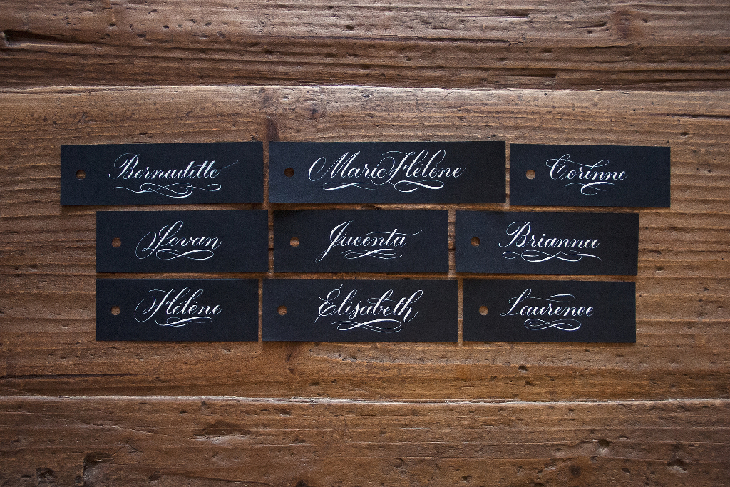 An array of nametags in fancy cursive writing.