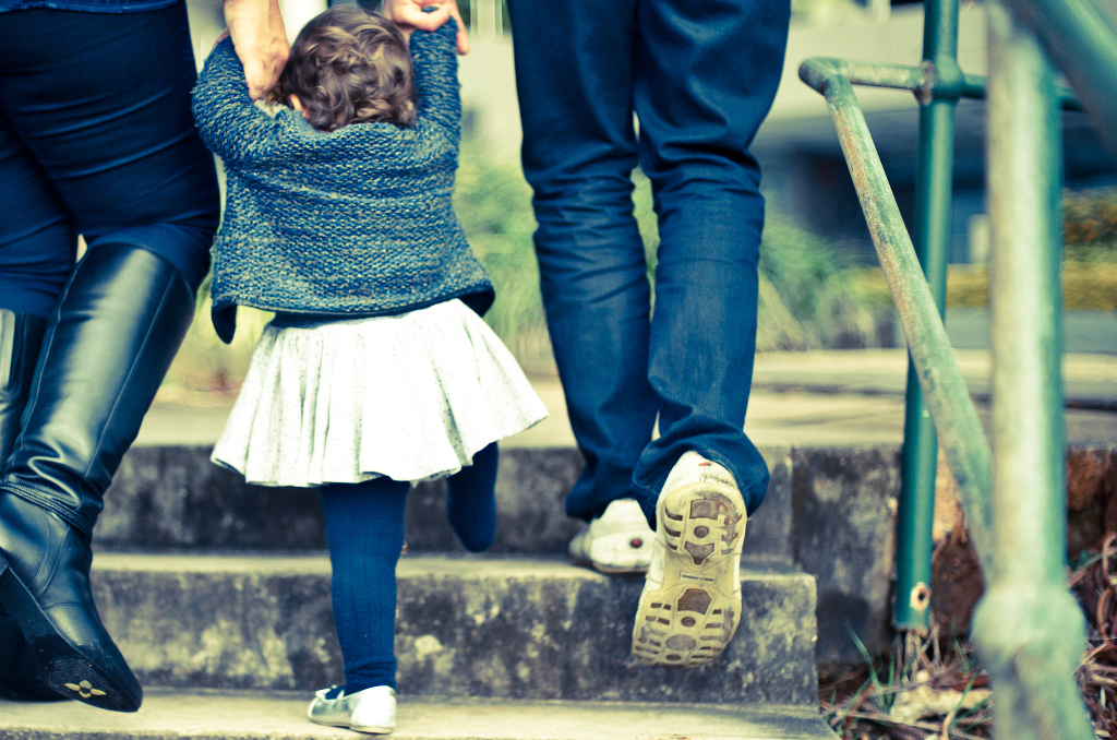 Two people helping a young child clamber up a flight of steps