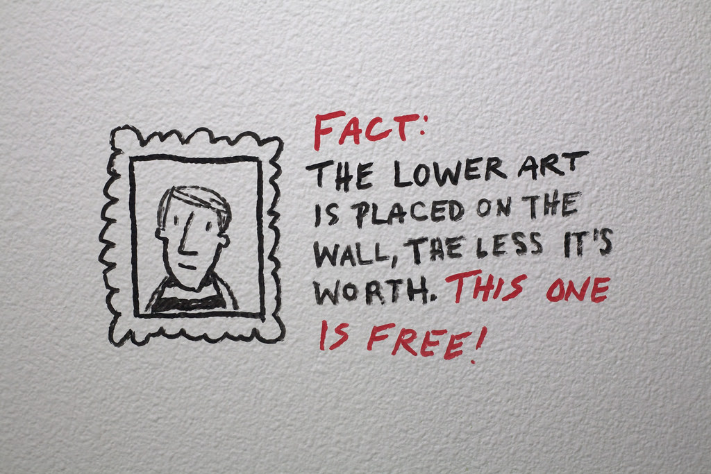 Graffiti advising the viewer that the lower art is placed on the wall, the less it is worth.