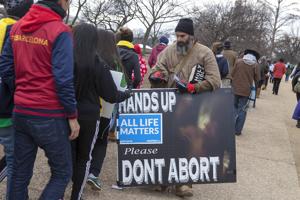 A man at an antichoice march holding up an ALL LIVES MATTER sign that includes the words HANDS UP DON'T ABORT.