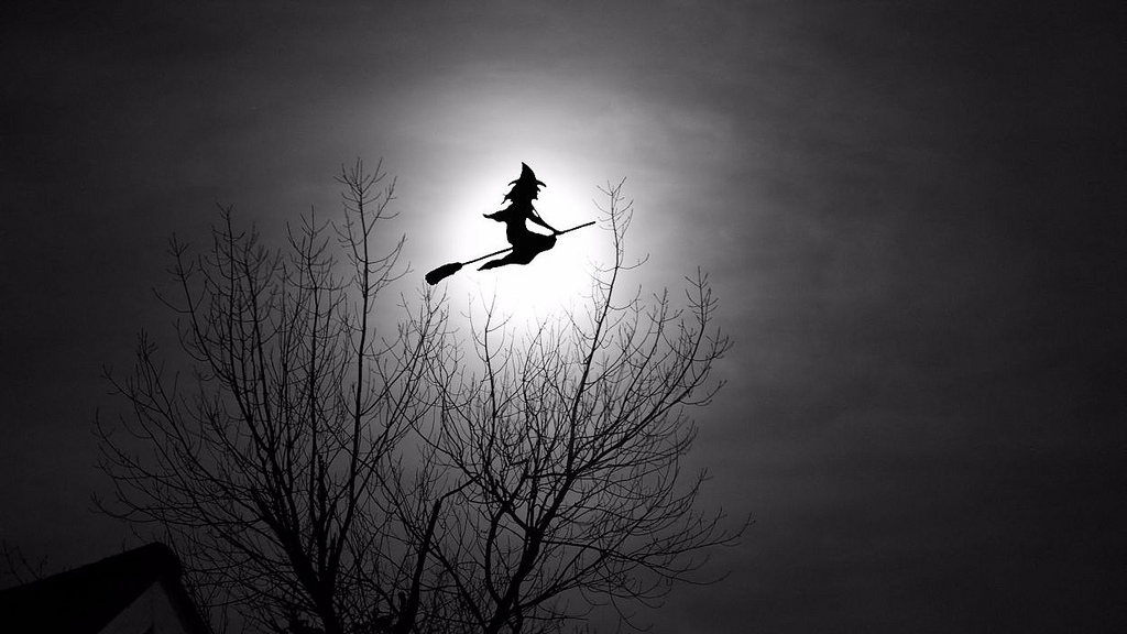 A silhouette of a witch on a broomstick crossing the moon.