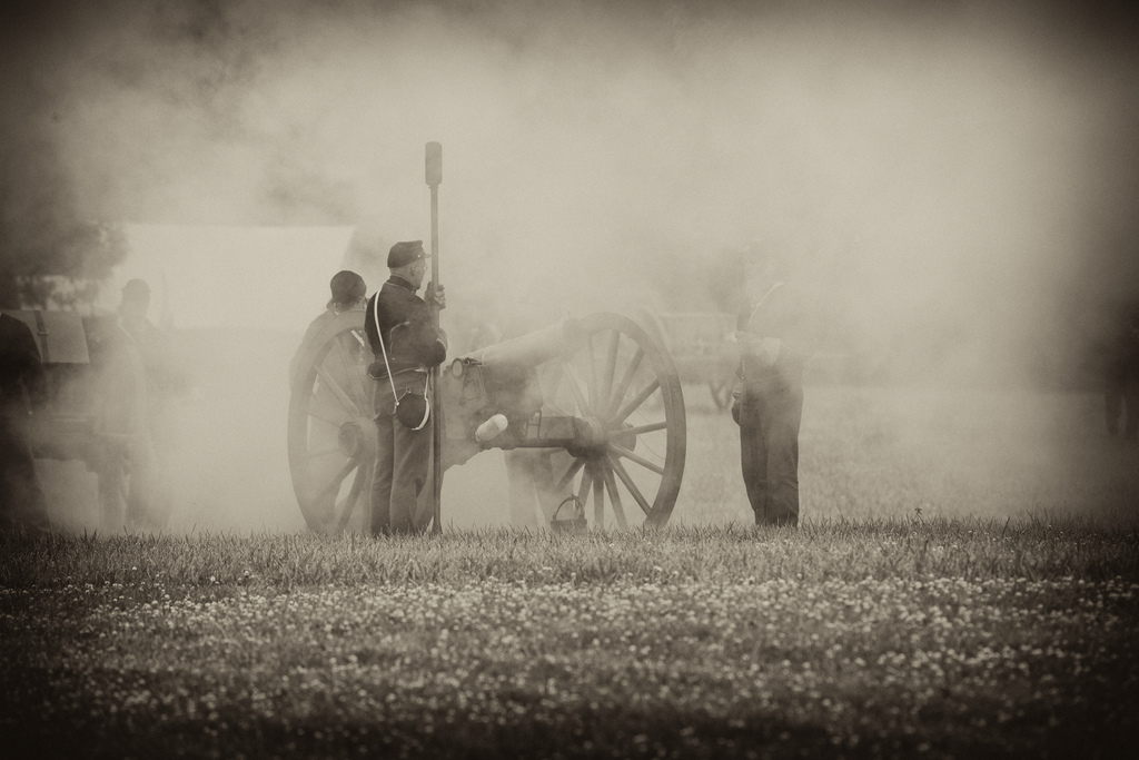 A Civil War reenactment, with smoke surrounding a cannon.