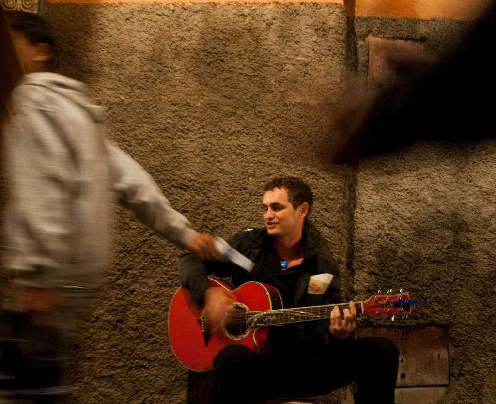 A musician busking for donations.