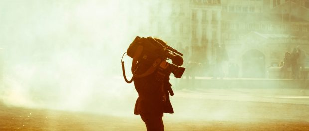 A camerawoman walking in a dusty street.