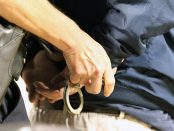 A pale-skinned person being handcuffed.