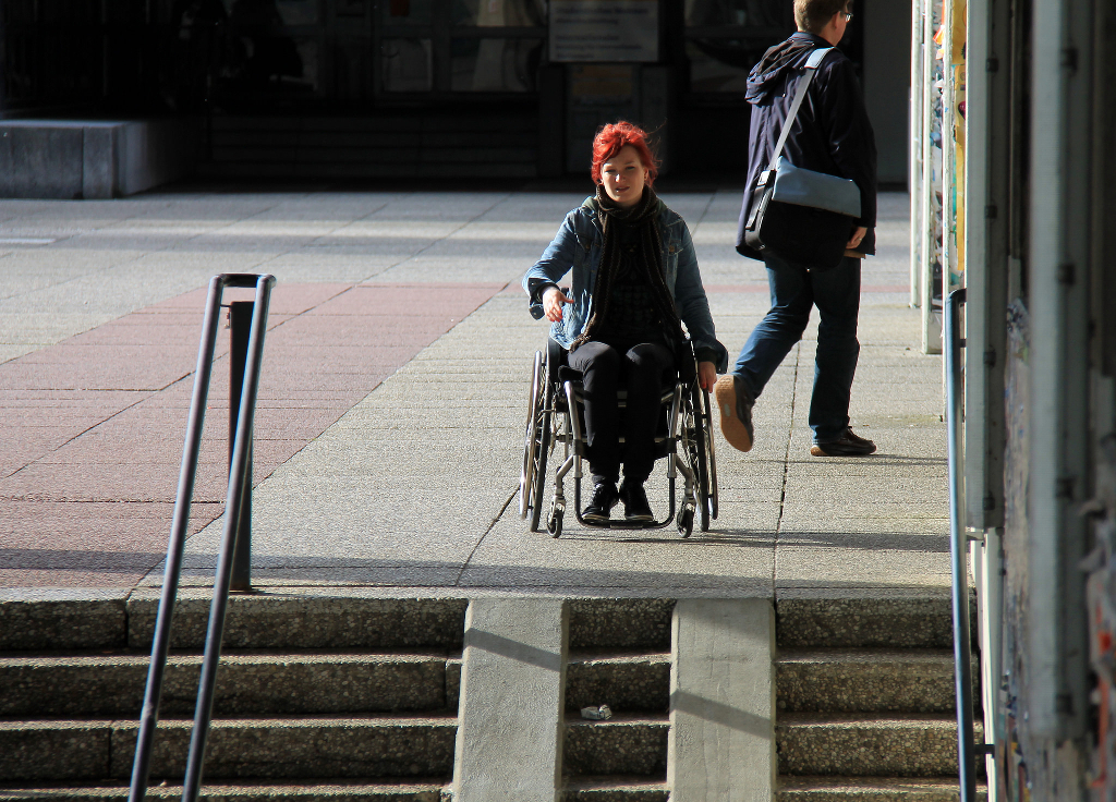 A wheelchair user with bright red hair at the top of a flight of steps.