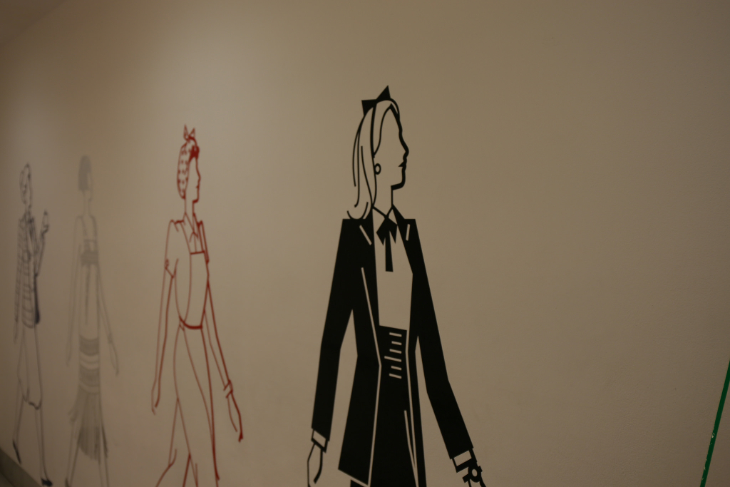 Stencils of women in various vintage costumes along a wall.