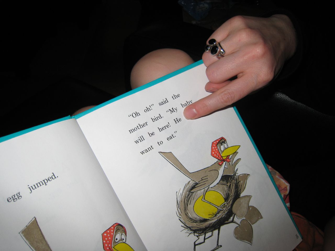 A parent reading a Dr. Seuss book to a child.