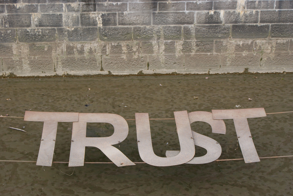 A broken sign reading TRUST.
