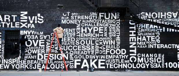 A painter working on a black and white mural with a word cloud against a brick background.