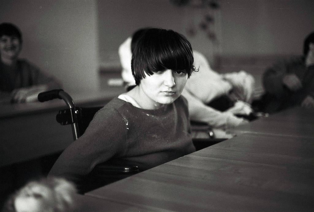 A disabled young person seated at a table.