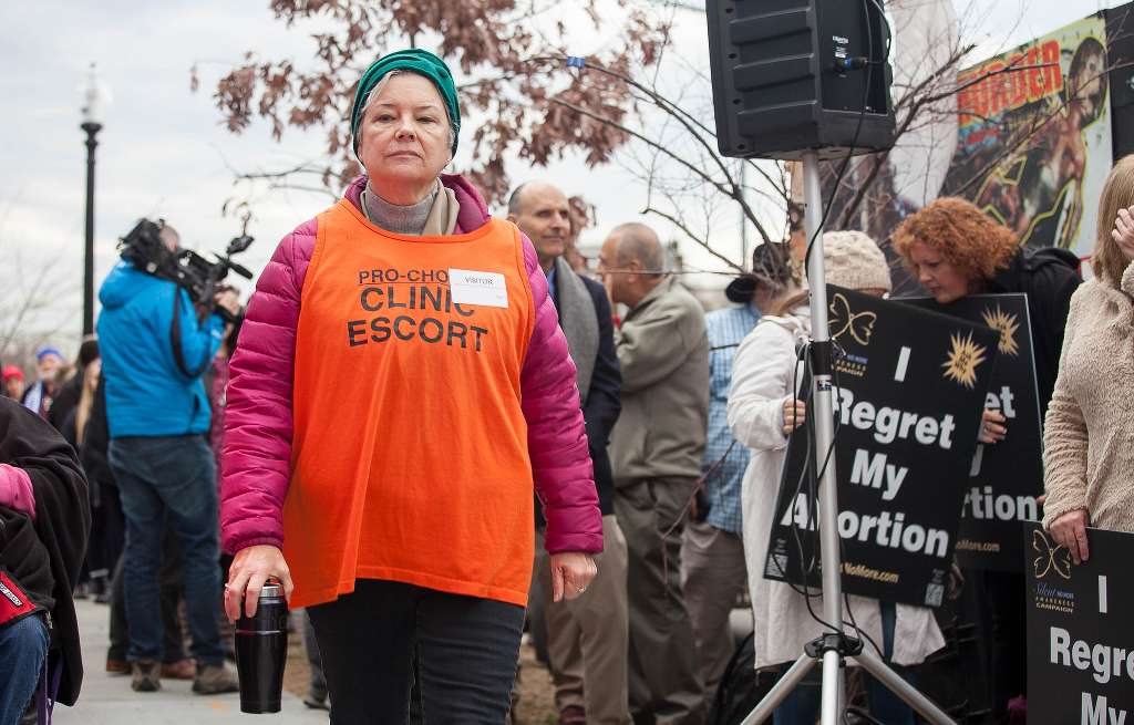 A clinic escort navigating an anti-choice throng.