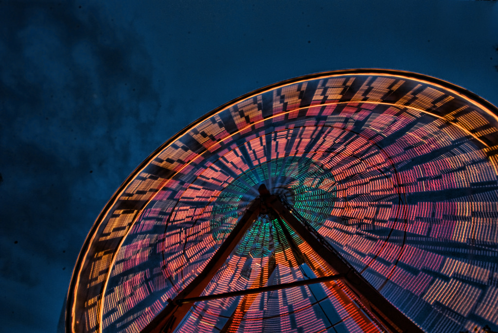 A Ferris wheel at night illuminated in a blaze of colour.