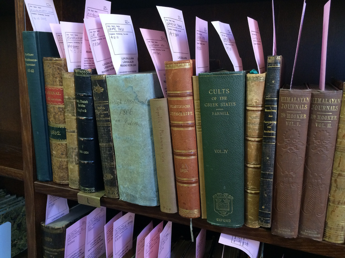An array of books with call slips tucked into their covers.
