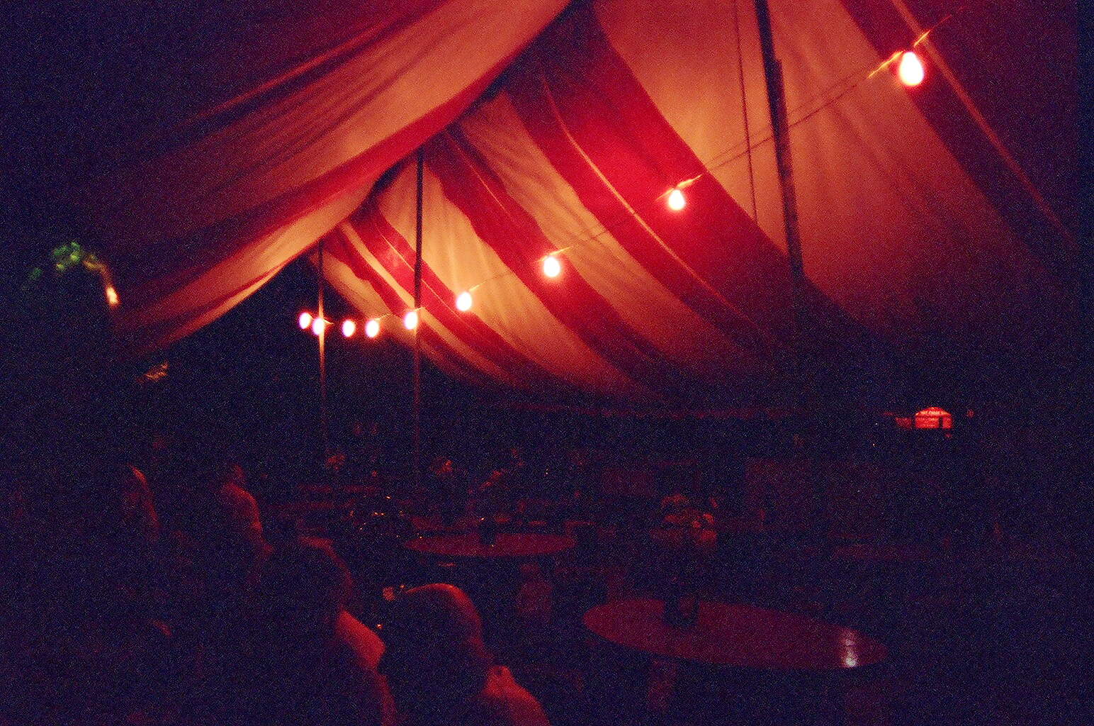 A dimly-lit tent filled with people eating dinner.