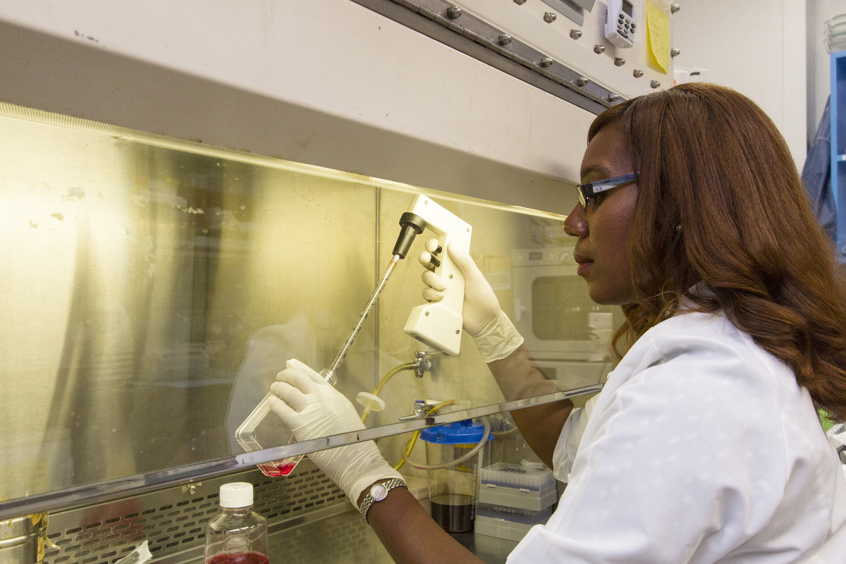 A dark-skinned person performing research at a lab bench.