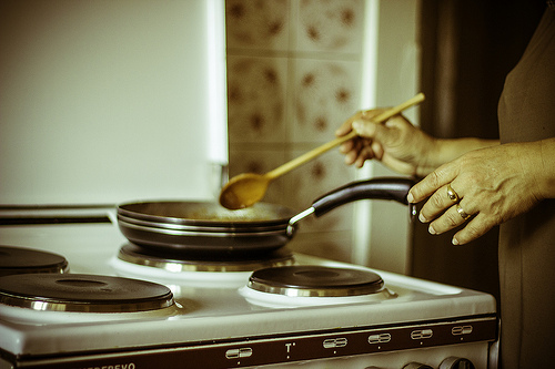 An image of a dish on the stove, a woman's hands visible at the edge of the frame. The photo has been treated to look retro.