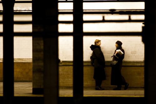 Two women talking on a subway platform, seen from across the station.