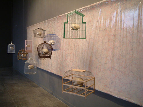 An art installation of model brains suspended in brightly painted birdcages.