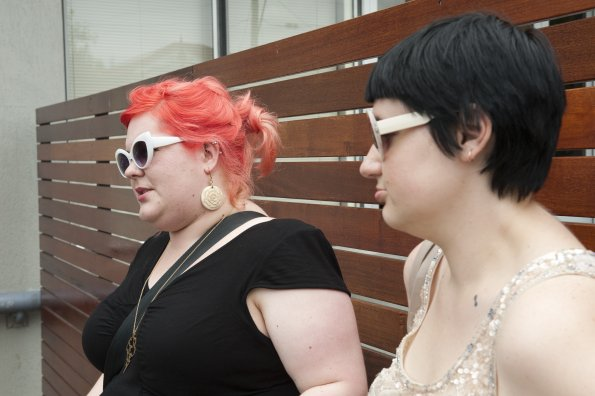 Two fat people stand next to a wooden wall, wearing sunglasses