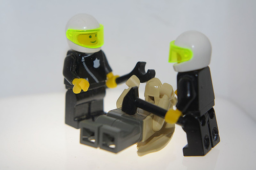 Two LEGO police officers beating up another LEGO figure.