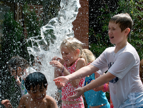 Children playing in a water fountain.
