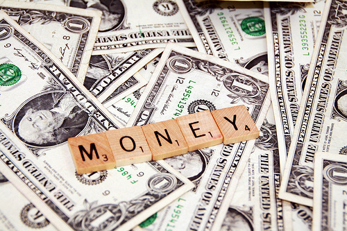 A pile of money topped by Scrabble tiles spelling out the word MONEY.